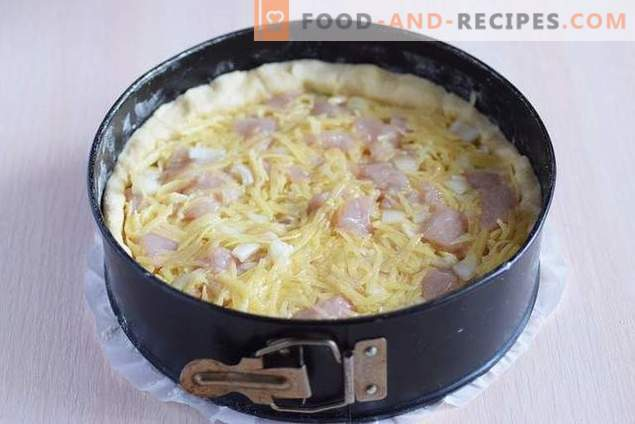 Open pie with chicken and potatoes under cheese crust