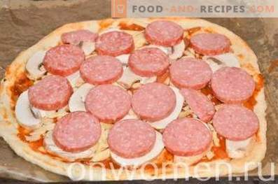 Pizza with sausage and mushrooms on yeast dough